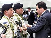 Presidente de El Salvador, Elías Antonio Saca (der) condecora a uno de sus soldados apostados en Irak.