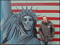 Paul Kenyon standing next to anti-American graffiti outside the former US embassy in Tehran