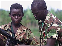 Child soldier, left, in Sierra Leone