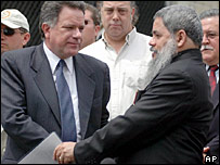 ELN leader Francisco Galan, right, shakes hands with Colombian Peace Commissioner, Luis Carlos Restrepo