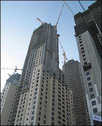Tall buildings in Dubai, with a backdrop of cranes