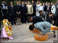 Lien Chan kneels at his grandmother's grave