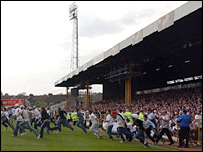 Swansea fans stream onto the pitch after the last ever league game at the Vetch.