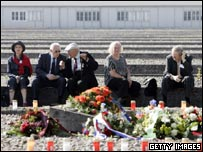 Camp survivors sit where the barracks used to stand in Dachau, Germany