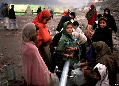 Women get water in a camp in Muzaffarabad, in Pakistani-administered Kashmir
