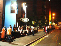 People wait outside their city centre hotel