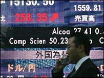 A Japanese man passing a board showing share prices