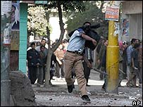 An Egyptian government supporter throws a stone during clashes with Muslim Brotherhood supporters