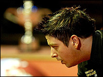 Matthew Stevens contemplates a shot during the World Snooker final, with the trophy in the background