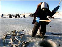 Catching fish through an ice hole.  Image: AP