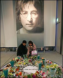 A Japanese couple lay flowers in John Lennon's memory