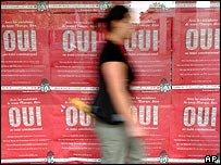 A woman walks past posters calling for a Yes vote on the ratification of the European constitution, in the streets of Bayonne, south-western France