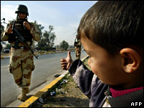 "An Iraqi boy gives a ""thumbs up"" to an Iraqi soldier"