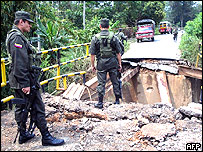 Colombian police officers stand guard on a blown-up bridge