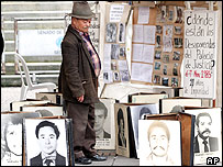 A man in Bogota looks at photos of the disappeared and killed