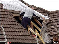 A villager begins to make repairs after the tornado that hit Hoghton
