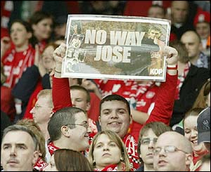 A Liverpool fan holds up a poster