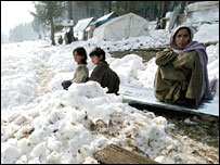 Kashmiri earthquake survivors sit outside a tent