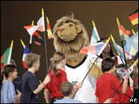 """La mascota oficial del torneo 'Goleo"""" rodeada de niños con banderas"""