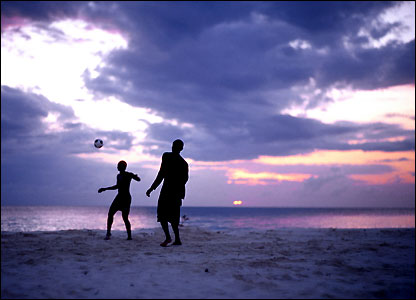 Footballers in on a beach as the sun sets in Tanzania