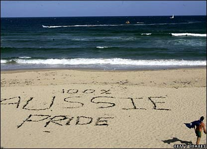 A man wearing an Australian flag walks past a slogan on the sand on Cronulla Beach, Sydney