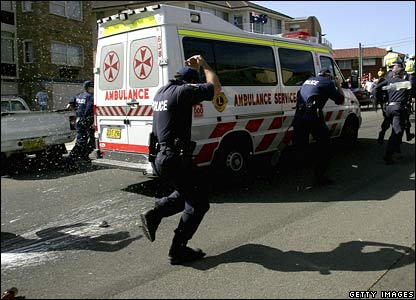 Police escorting an ambulance are pelted with glass bottles, Cronulla Beach