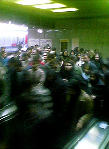Men and women crowd around escalators in Tehran metro train station