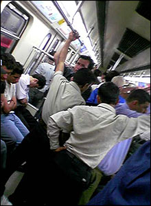 Commuters stand holding onto handrails in Tehran metro train