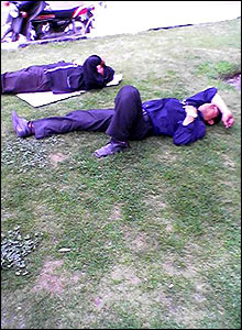 Men in suits lie on grass in the shade