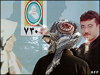 Kurdish elector looks at campaign poster