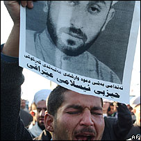 An Iraqi mourner carries a picture of slain Sheik Norzad Taher, a member of the Guidance and Islamic Call group, during his funeral procession in Kirkuk, Iraq