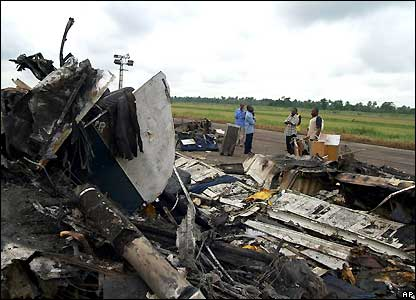 People stand near the wreckage of the plane that crashed at the airport in Port Harcourt, Nigeria