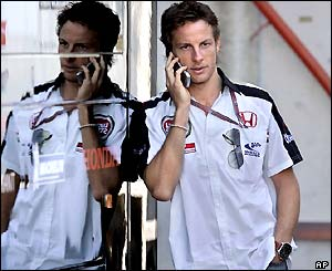 Jenson Button talks on a mobile phone at the Barcelona circuit