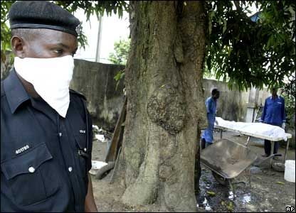 A policeman stands guard near a dressed corpse waiting to be taken away outside a mortuary in Port Harcourt