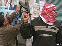 Gunmen guard a party working putting up posters in Ramadi