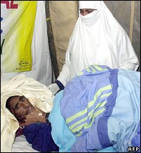 A Pakistani paramedic takes care of Naqsha who lies in a hospital in Muzaffarabad