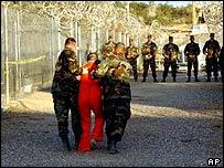 Prisoner accompanied by guards at Guantanamo