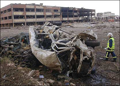 A devastated warehouse and car