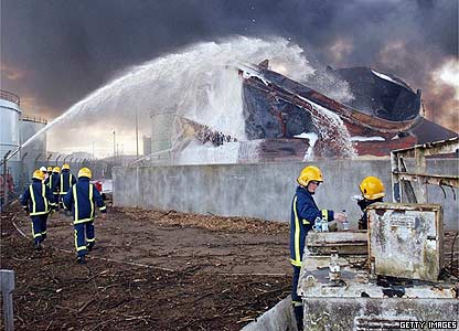 Firefighters tackle a burning oil tank