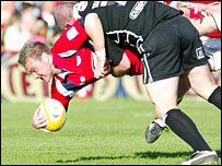 Scarlets fly-half Ceiron Thomas is tackled by Steve Tandy
