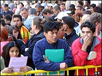 Immigrants wait outside a government office in Madrid to apply for residency