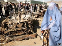 Afghan woman passes by a destroyed jeep of the ISAF vehicle destroyed suicide car bomb attack targeting the Nato forces