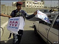 Iraqi policeman handing out UIA posters