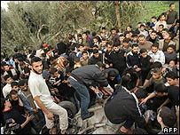 Palestinians gather around the wreckage of the attacked car