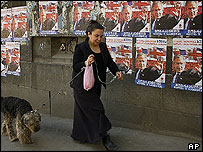 A Georgian woman with her dog passes by posters of George W Bush
