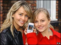 Cast members of Coronation Street hold up mobile phone
