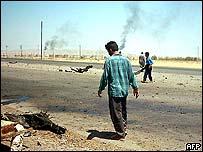 Iraqi surveys debris from roadside bomb in Bayji, Iraq.