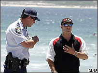 A policeman stands by as local beachgoer Douglas Briancourt protests the loss of peace at Cronulla Beach, 15 December 2005.
