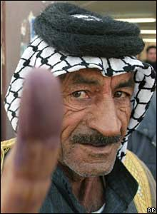 An Iraqi man shows his finger stained with ink signifying he has voted