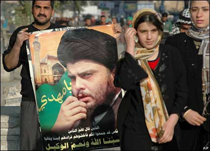 A man holds a portrait of Shia leader Moqtada al-Sadr